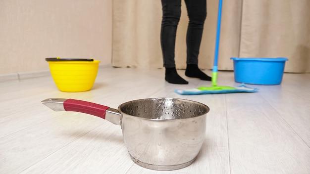 비가 온 후 천장에서 금속 냄비로 물이 떨어지는 동안 여성은 밝은 거실 가까이에서 다채로운 세면대로 젖은 바닥을 닦습니다