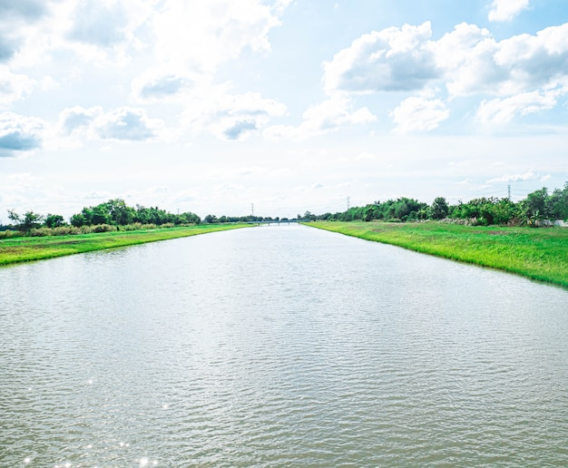 Водопроводные и распределительные каналы. ирригационный канал, вдоль которого пролегает тропа среди зеленых полей и голубого неба. красивый пейзаж в банг лен, накхонпатхом, таиланд