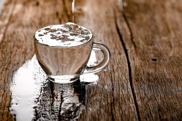 Water in cup on wooden background