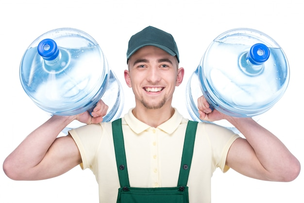 Water delivery courier is holding a two bottles.