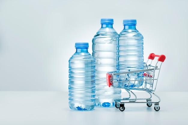 Служба доставки воды. различные бутылки с водой на светлой поверхности с местом для текста.