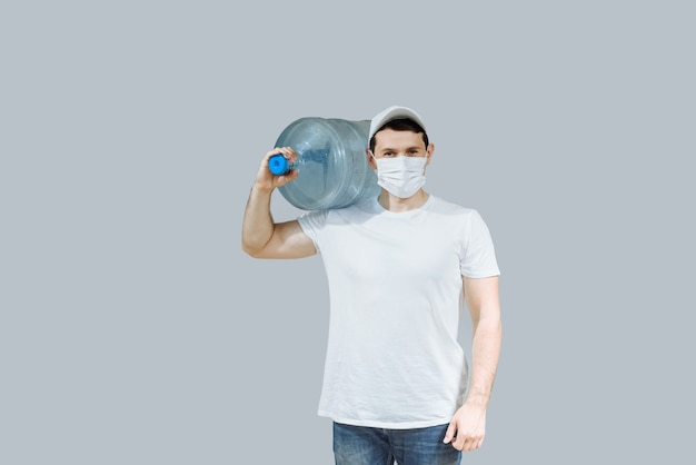 Water deliveryman with gloves with a bottle of water on his shoulder