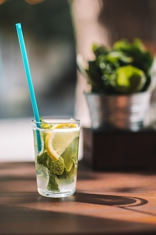 Water detox with lemon and mint on a dark wooden background.