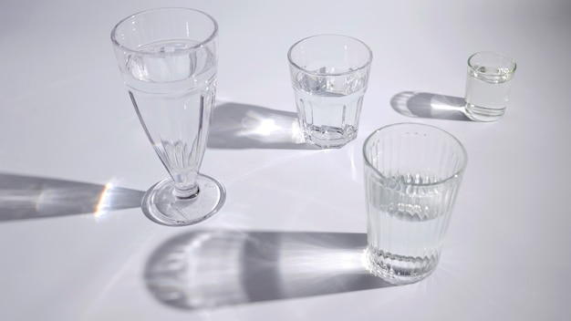 Water in the different type of glasses with shadow on white backdrop