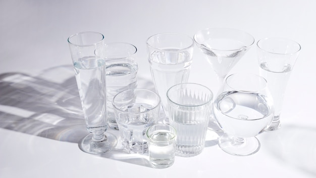 Water in different type of glasses with shadow on white background