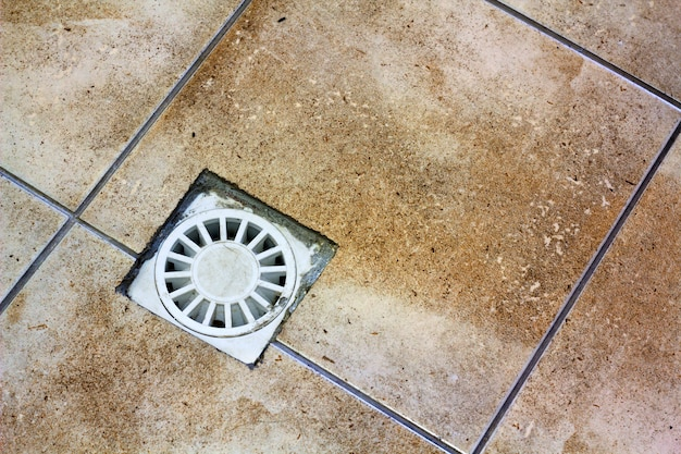 Water drain vent in kitchen, bathroom or basement ceramic tiled old vintage floor.