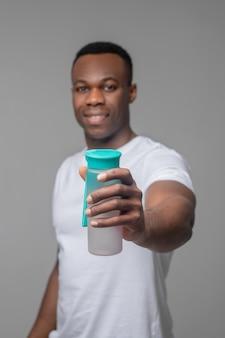 Water, drink. benevolent joyful darkskinned muscular man holding out bottle of water standing against light background