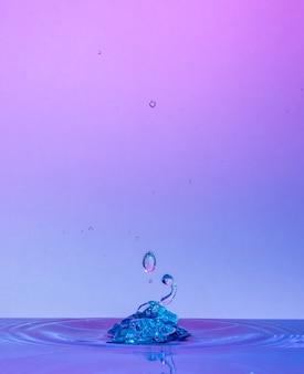 Макро-фотография столкновений капель воды с розовым и синим фоном