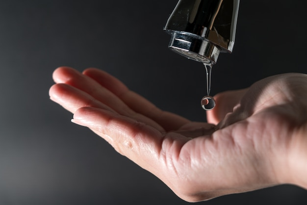 Water drop on faucet with black background