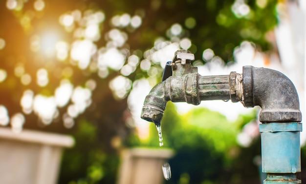 Капля воды из крана на фоне зеленого