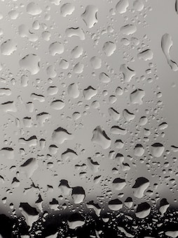Water drop on the glass of windows background, raining on the glass off window city for background.