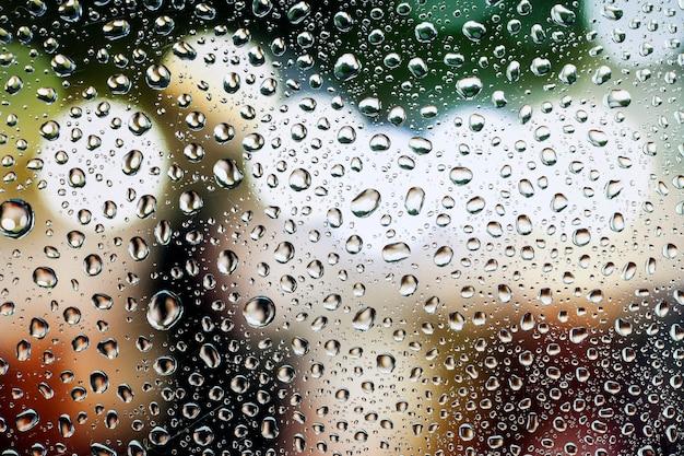 Капля воды, капля дождя на стекле с красивым фоном