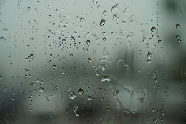Капли воды на стеклянном окне с размытым призраком, похожим на каплю воды за пределами тени
