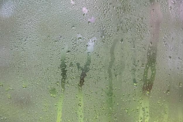 Капля воды на черном грунтовом стекле
