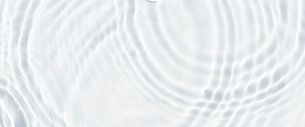 Water droplets fall on the transparent surface of the water in sunlight. top view, flat lay. banner.