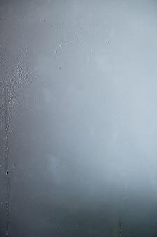 色付きの背景を持つガラスに水滴。水滴。