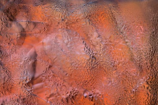 色付きの背景を持つガラス上の水滴