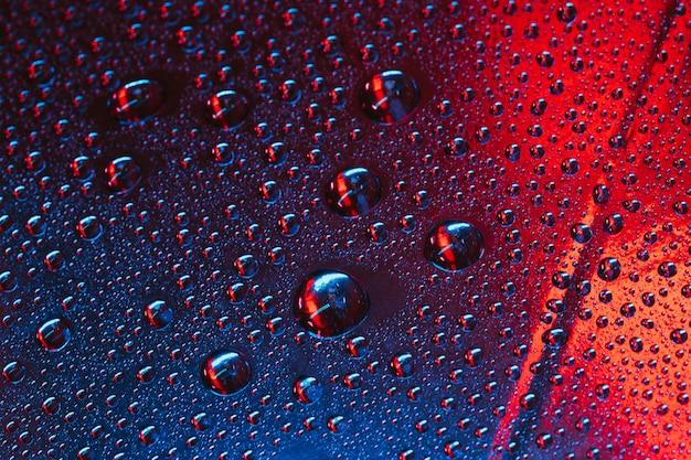 赤と青の織り目加工の背景を持つガラス上の水滴