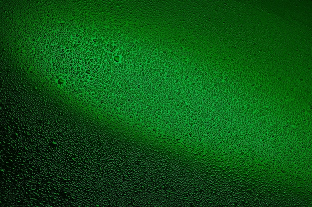 Water drops on black glass. background illuminated with green