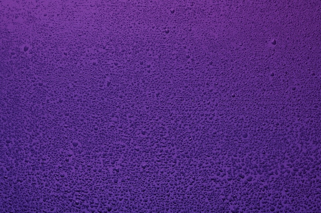 Water drops on black glass. background illuminated with lilac