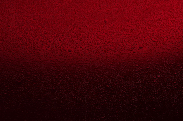 Water drops on black glass. background illuminated with red l