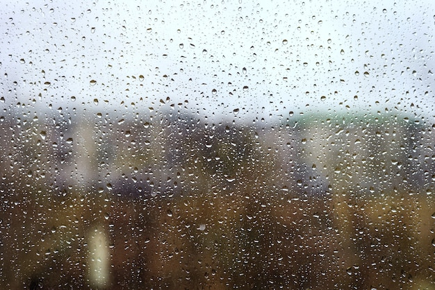 Water drops from rain on the window glass against the urban landscape, tinted