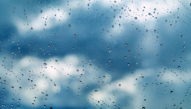 Water drops on glass, on sky background, background or texture
