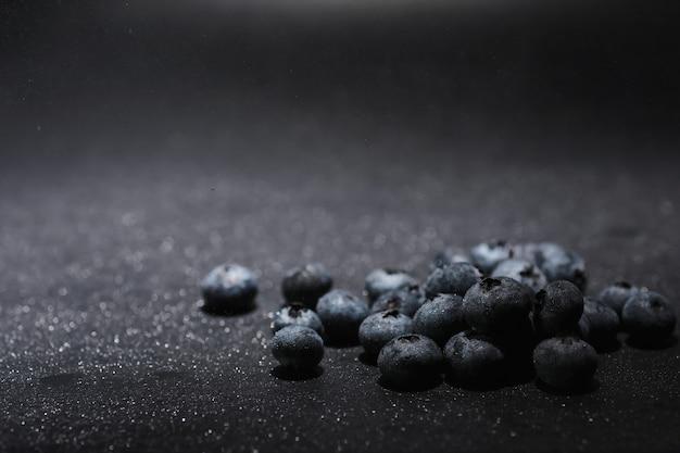 熟した甘いブルーベリーに水滴。あなたのテキストのためのコピースペースと新鮮なブルーベリーの背景。ビーガンとベジタリアンの概念。ブルーベリーベリーのマクロテクスチャー。テクスチャーブルーベリーベリーのクローズアップ
