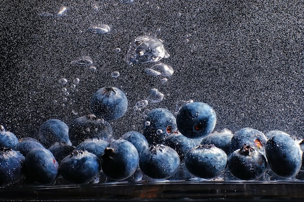 熟した甘いブルーベリーに水滴。あなたのテキストのためのコピースペースと新鮮なブルーベリーの背景。ビーガンとベジタリアンの概念。ブルーベリーベリーのマクロテクスチャー。