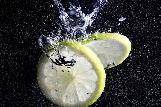 熟したスイートレモンに水滴。あなたのテキストのためのコピースペースと新鮮なライムの背景。ビーガンとベジタリアンの概念。
