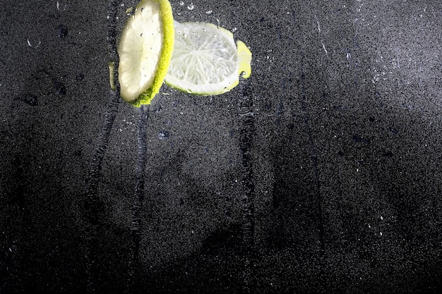 熟した甘いレモンに水が落ちる。あなたのテキストのためのコピースペースと新鮮なライムの背景。ビーガンとベジタリアンの概念。