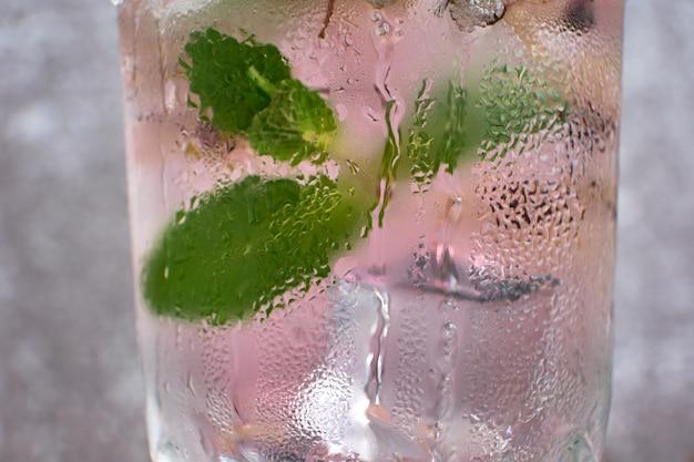 Капли воды на поверхности стекла с ледяным напитком с мятой