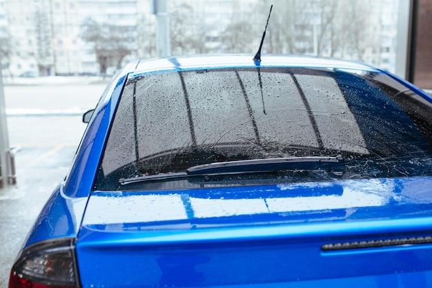 Вода падает на заднее стекло автомобиля. концепция автомойки