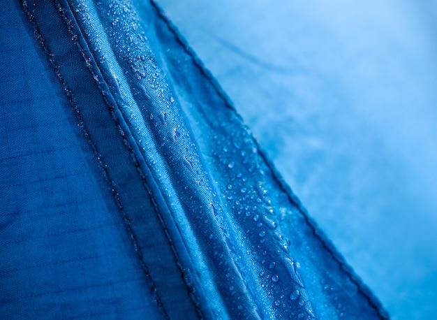 防水膜生地に水滴。青い合成防水布の質感の詳細図。テントの朝露。