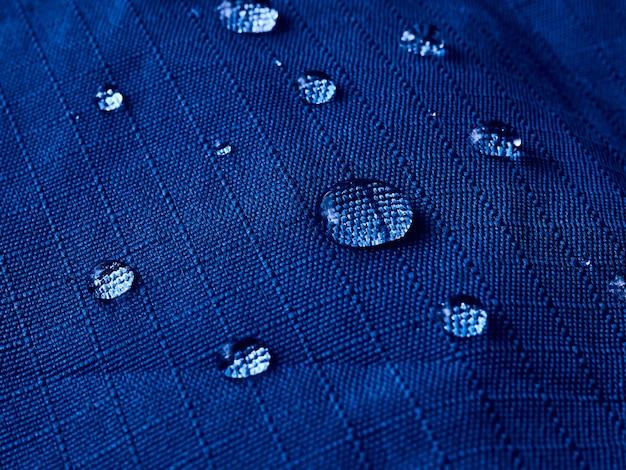방수 멤브레인 원단에 물방울이 떨어집니다. 파란색 방수 천의 질감의 상세보기.