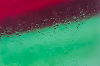 Water drops over the green and red painted background