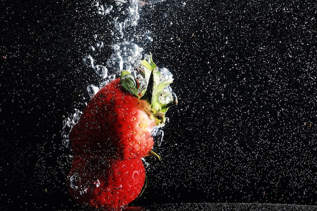Water drops on ripe sweet strawberry. fresh berry background with copy space for your text. vegan food concept.
