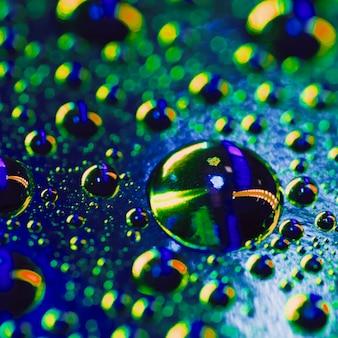 Gocce d'acqua sulla superficie con una riflessione colorata lucida