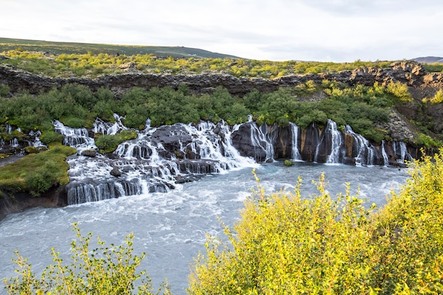 Water falls from all sides to the river in barnafoss in summer. iceland