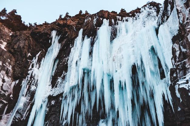 Вода падает на коричневую скалистую гору днем
