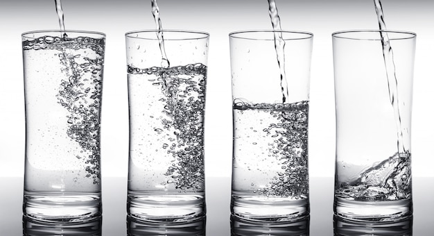 Water filling glasses in sequence
