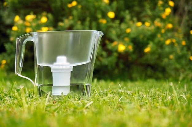 Фильтр для воды, стоящий на зеленой траве в летнем саду с красивыми цветами, растущими на кустах на заднем плане
