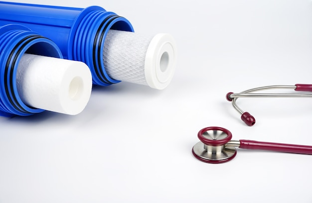 Water filters carbon cartridges and stethoscope on white background household filtration system