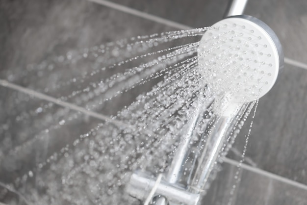 물방울의 레인 샤워기에서 호텔 욕실로 물이 흐릅니다.