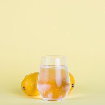 水のガラスと黄色の背景にレモン