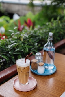 Acqua in una bottiglia di vetro latte ghiacciato su un supporto rosa sale e carta sul tavolo di legno