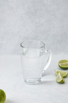 Water in glass cup with lime on light grey background with copy space. morning detox drink.