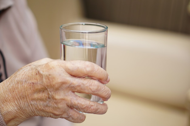 Water glass in the hand an senior or asian elderly old lady woman. healthcare, love, care, encourage and empathy.