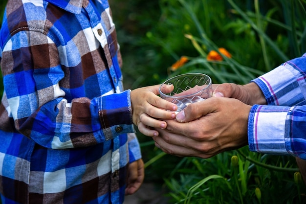 Water in a glass in the hands of a child and father. nature. selective focus