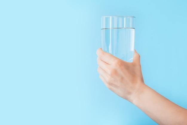 Стакан воды в женской руке на цветном синем фоне копией пространства. концепция фитнеса здорового образа жизни